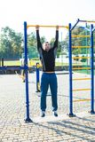 The man workout on the crossbar. Man in sportswear performs pull-ups on the crossbar on a sports ground royalty free stock photo