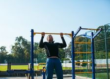 The man workout on the crossbar. Man in sportswear performs pull-ups on the crossbar on a sports ground royalty free stock image