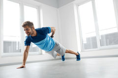 Man Workout Exercises. Fitness Male Model Doing Push Ups Indoors Stock Photography