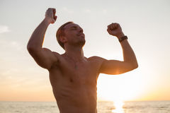 Man after workout standing in the sunset. Happy man after workout standing in the sunset Stock Image