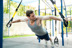 Man during workout with suspension straps on the street. Trx Royalty Free Stock Photos