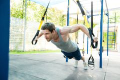 Man during workout with suspension straps on the street. Trx Royalty Free Stock Image