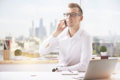 Man at workplace talking on phone Stock Photography