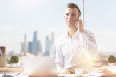 Man at workplace talking on phone Royalty Free Stock Photo