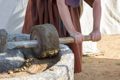 Man works at ancient Roman press for olive oil Royalty Free Stock Images