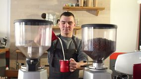 A man Barista works in a modern coffee shop, he pours milk into a Cup of coffee. stock video