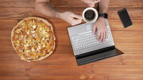 A man works behind a laptop and eats pizza. Nearby there is a coffee mug. Wooden table top view stock video footage