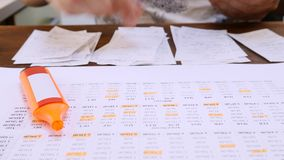 Man Works with Bills Counting Annual Family Budget. On table with smartphone and orange marker. Calculating income and expenses. Family monthly payments stock video