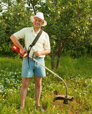 Man works with cordless grass trimmer Royalty Free Stock Photo