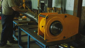 Man works at factory with metal bar. Engineer operates machine, assistant helps carefully move steel stock video footage
