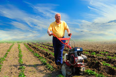 Man works in the field. Man in the field with the motor cultivator Stock Image