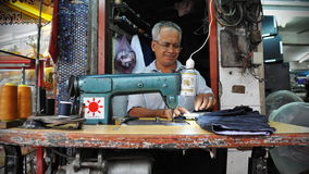 Man Works at a Garments Shop. A man operates a sewing machine at a streetside garments shop on January 27, 2012 in Bangkok, Thailand. Textile and clothing is Stock Photography