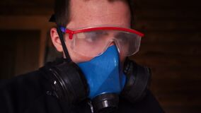 a man works indoors in goggles and a respirator.