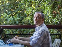 A man works on a laptop in the garden stock photos