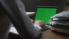 Man works at laptop late ot office with Green Screen. Businessman working at night at the computer with Choma Key. stock footage
