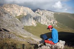 A man works on a laptop sitting on top of a mountain. Office in the mountains stock photos
