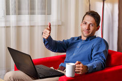 Man works for laptop. Thumb up. Man works for laptop. Businessman holding a cup of coffee and shows thumb up. Freelancer at work. Life is good Stock Photo