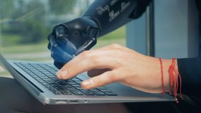 Man works with a laptop, wearing a bionic hand. Cyborg concept. One man works with a laptop, wearing a bionic hand