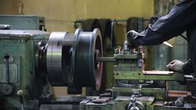 A man works with a lathe. Routes material to the turning element. Side view stock video footage