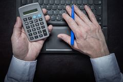 Man works in the office and holds his calculator and pen Stock Photography