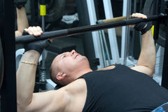 Man works out. On a weight bench Royalty Free Stock Image