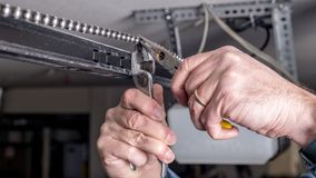 Man works with pliers to repair a garage door opener chain. Tools are used to work on a garage door opener chain royalty free stock photos