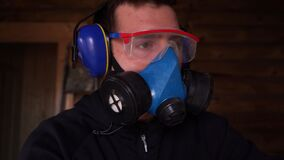 man works in a respirator, goggles and earmuffs to protect eyesight, breathing
