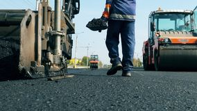 Man works on a road with machines, laying asphalt.