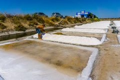 Man works salt extraction food industry. Baths with salt, in Vila real Santo Antonio, Portugal.  stock photos