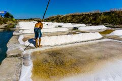 Man works salt extraction food industry. Baths with salt, in Vila real Santo Antonio, Portugal.  stock image