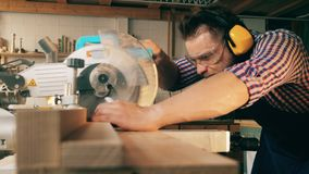 A man works with saw bench while cutting wood at a workshop. stock video