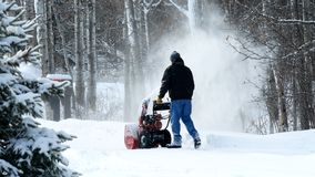 Man works with a snow blower to remove newly fallen snow from driveway. After storm in Minnesota. Video footage available stock image
