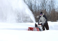 A man works snow blowing machine Stock Photography