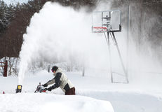 A man works snow blowing machine Royalty Free Stock Photography