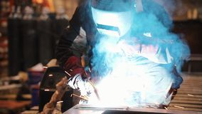 A man works with a welding machine and using a torch