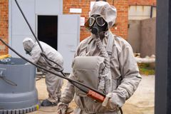 Man works in a white chemical protection suit and a gas mask. stock photos