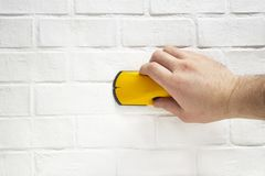 Man works with a wireless building tool to detect wooden battens on the background wall brick. Man works with a wireless building tool to detect wooden battens royalty free stock photography