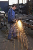 Man at workshop. Man working with angle grinder on steel construction at industrial workshop stock images