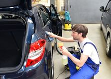 Man in a workshop cleaning a car - service for the customer. In a company Stock Photo