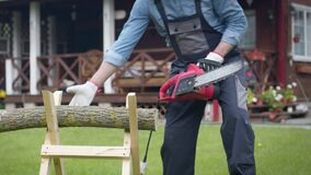Man in workwear saws firewood on sawhorses with an electric saw at his home site