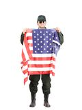 Man in workwear stands with american flag. Stock Photo