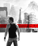Man of the world. Fine art black and white concept photo of a young man in front of a blurred cityscape background with bold red horizontal stripe Stock Photo