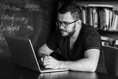 Man worn glasses. Software Engineer is sitting and working. He is looking into his laptop. Black and white photo Stock Image