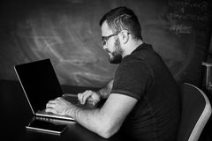 Man worn glasses. Software Engineer is sitting and working. He is looking into his laptop. Black and white photo Royalty Free Stock Photos