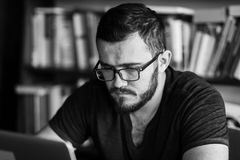 Man worn glasses. Software Engineer is sitting and working. He is looking into his laptop. Black and white photo Stock Photo
