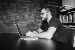 Man worn glasses. Software Engineer is sitting and working. He is looking into his laptop. Black and white photo Royalty Free Stock Image