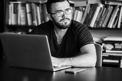 Man worn glasses. Software Engineer is sitting and working. He is looking into his laptop. Black and white photo Stock Images