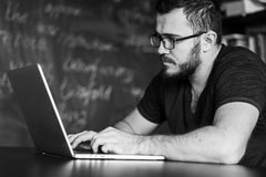 Man worn glasses. Software Engineer is sitting and working. He is looking into his laptop. Black and white photo Royalty Free Stock Photo