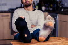 Man with worn out socks relaxing in kitchen Stock Image
