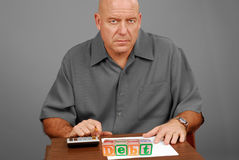 Man Worried About Debt. Man with calculator at desk with DEBT written in blocks royalty free stock photo